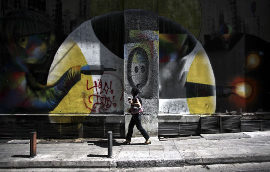 A woman walks past a mural at Athens downtown Athens photography weekend - street photography